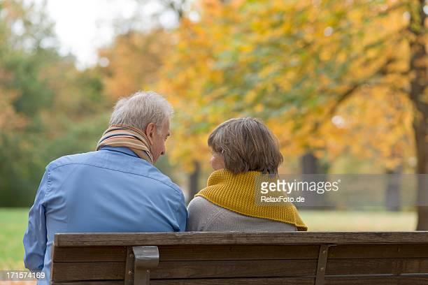 Senior couple assis sur un banc dans le parc en automne