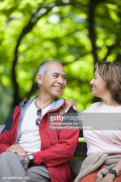 """senior couple sitting on park bench, looking in eyes and smiling - """"compassionate eye"""" fotografías e imágenes de stock"""