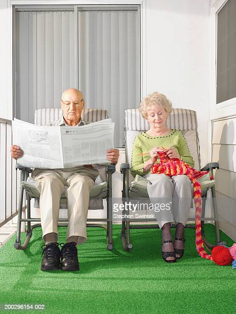 Senior couple sitting on patio, man reading paper, woman knitting