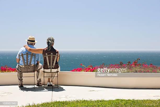 Senior couple sitting on patio overlooking ocean