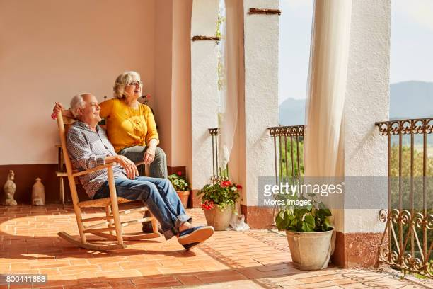 senior couple sitting on rocking chair at home - rocking chair stock photos and pictures