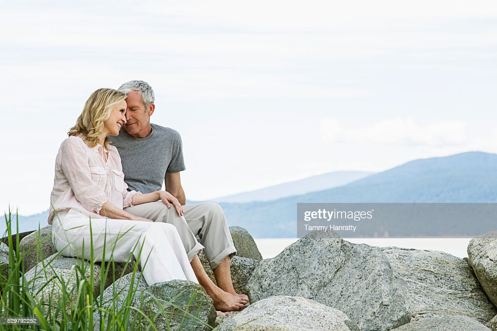 Senior couple sitting on rocks : Foto de stock