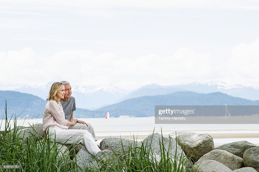 Senior couple sitting on rocks : Stockfoto