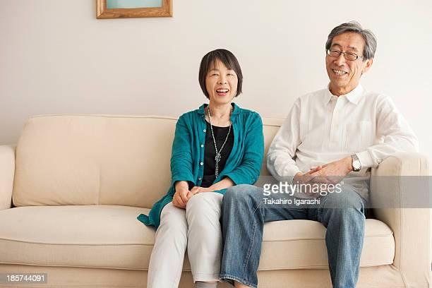 senior couple sitting on sofa,  portrait - 60代 ストックフォトと画像