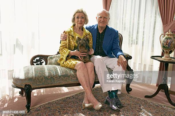 senior couple sitting on sofa, with dog, smiling, portrait - legs crossed at ankle stock pictures, royalty-free photos & images