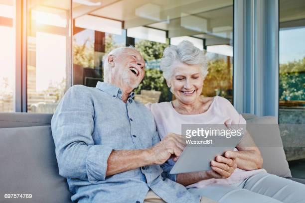 Senior couple sitting on terrace using digital tablet