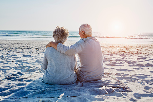 Senior couple sitting on the beach looking at distance - gettyimageskorea