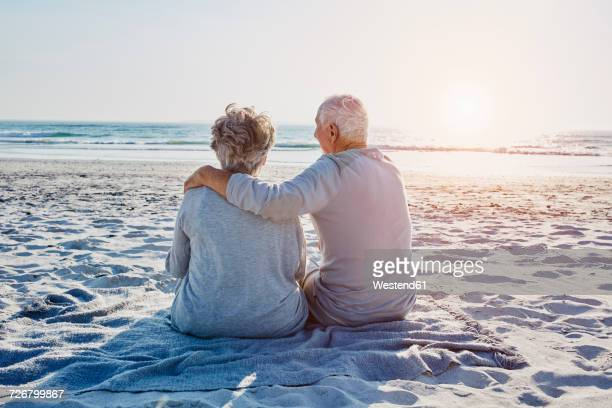 Senior couple sitting on the beach looking at distance