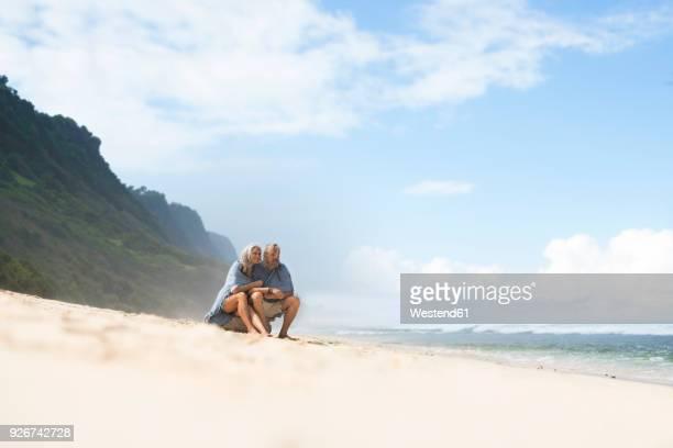 senior couple sitting on the beach, wrapped in a blanket - 60 64 anos - fotografias e filmes do acervo