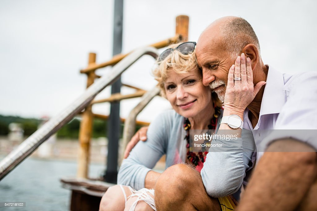 senior couple sitting on the jetty relaxing : Stock-Foto