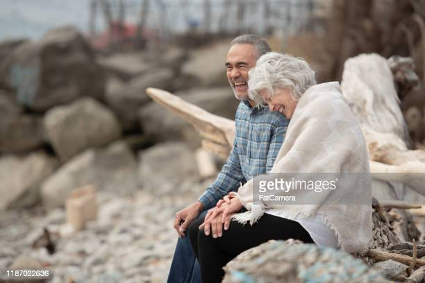 senior couple sitting on the shoreline stock photo - medicare stock pictures, royalty-free photos & images