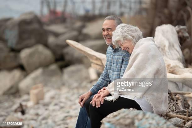 senior paar zittend op de shoreline stock photo - medicare stockfoto's en -beelden