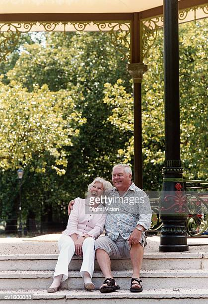 A Senior Couple Sitting on the Steps of a Park Pavilion