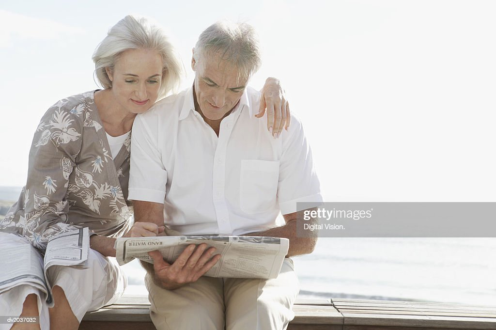 Senior Couple Sitting on Wooden Decking by the Sea and Reading a Newspaper : Stock Photo