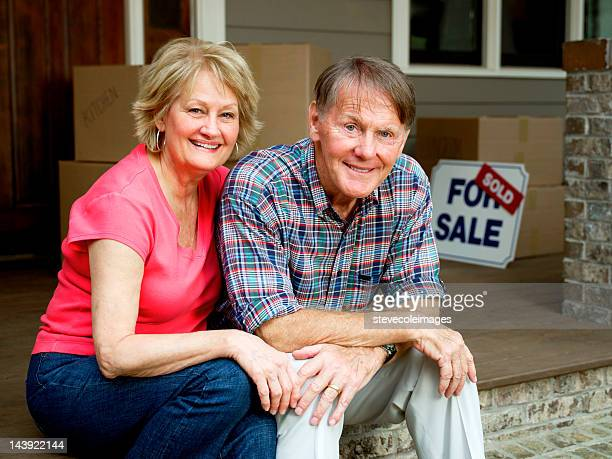Senior Couple Sitting Outside House With For Sale Sign