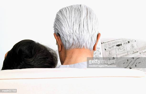 Senior couple sitting side by side, man reading cartoon section of newspaper, rear view, close-up, part of