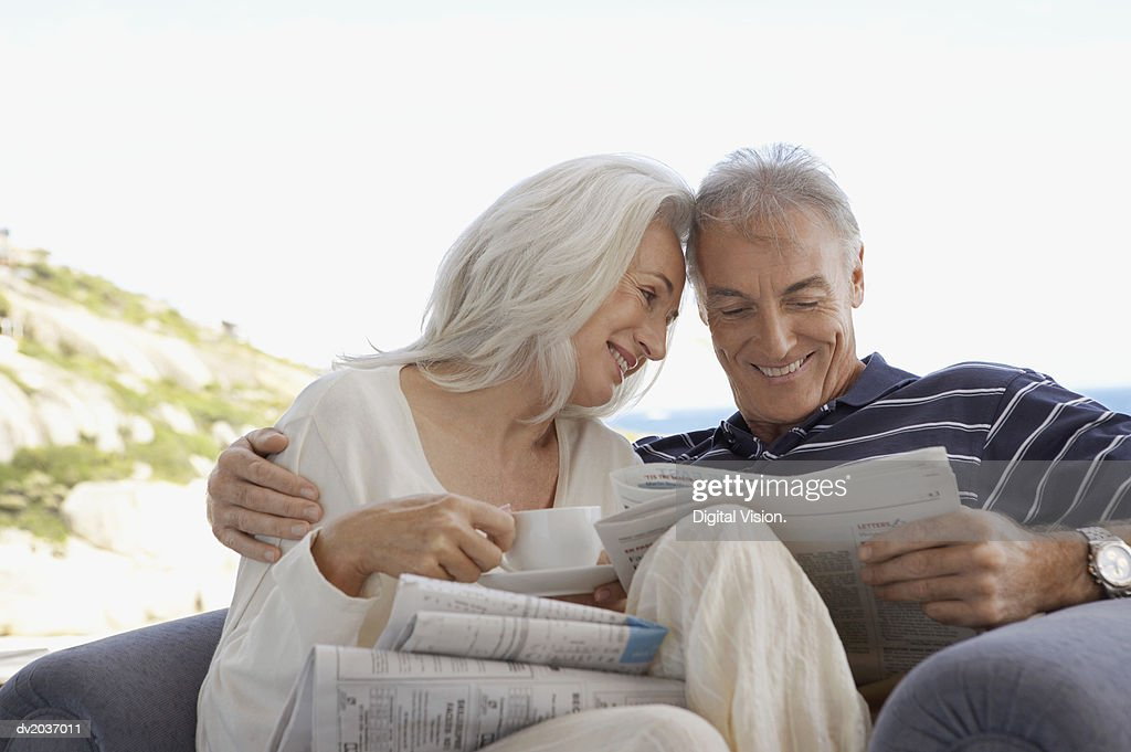 Senior Couple Sitting Together in an Arm Chair and Reading a Newspaper : Stock Photo