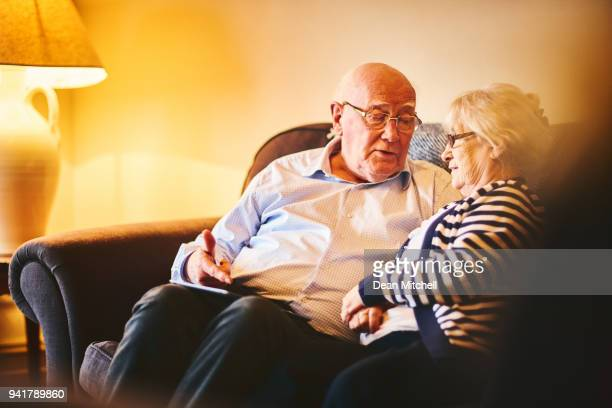 Senior couple sitting together with digital tablet and talking