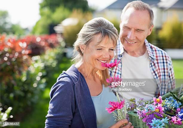 Altes Paar riechen Blumen im Garten