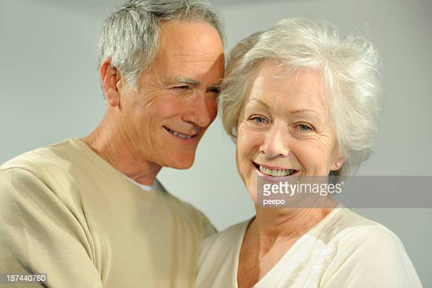A senior couple smiles happily in a headshot.