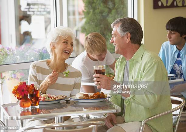 Senior couple smiling and eating at restaurant