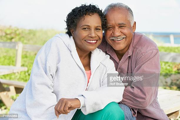 Senior couple smiling and hugging outdoors
