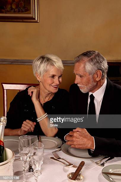 Senior couple smiling at each other at table