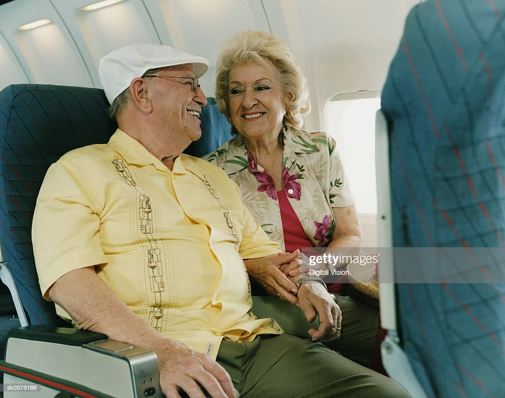 Senior Couple Smiling at Each Other on a Plane : Stock Photo