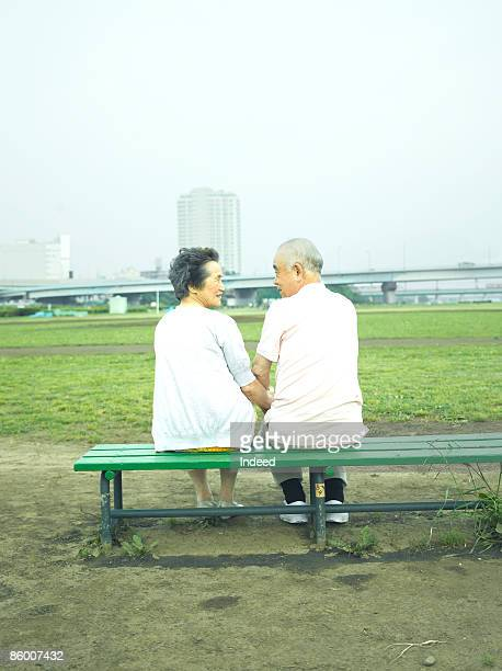 Senior couple smiling face to face on bench