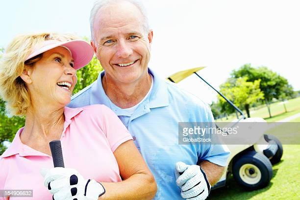 年配のカップルに笑顔、ゴルフをお楽しみください。