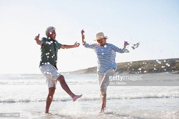 senior couple splashing in ocean - zorgeloos stockfoto's en -beelden