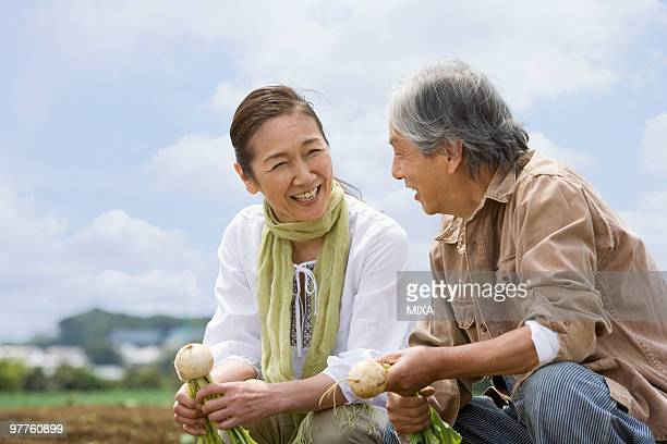 senior couple squatting on field - 60代 ストックフォトと画像