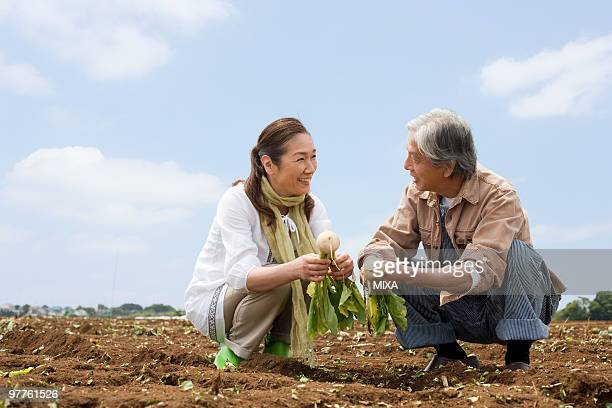 senior couple squatting on field - kanagawa prefecture stock pictures, royalty-free photos & images