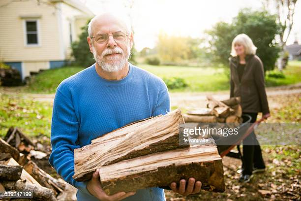 Senior Couple Stacking Firewood on the backyard