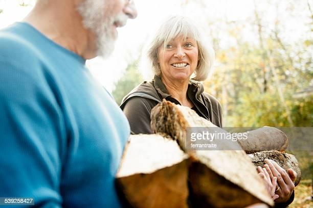 Couple Senior Amonceler Bois de chauffage sur la cour