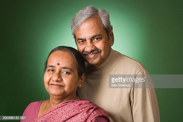 Senior couple standing against green background
