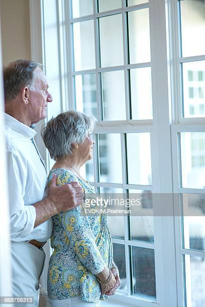 Senior couple standing and looking through window