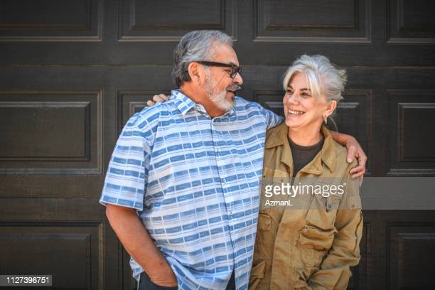 senior couple standing arms around against wall - arm around stock pictures, royalty-free photos & images