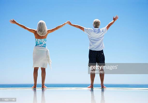 Senior couple standing at edge of infinity pool with arms outstretched