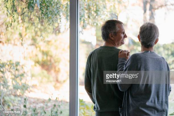 senior couple standing at panorama window - introspection stock pictures, royalty-free photos & images