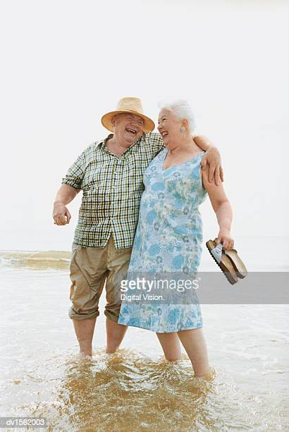 Senior Couple Standing at Water's Edge and Having Fun
