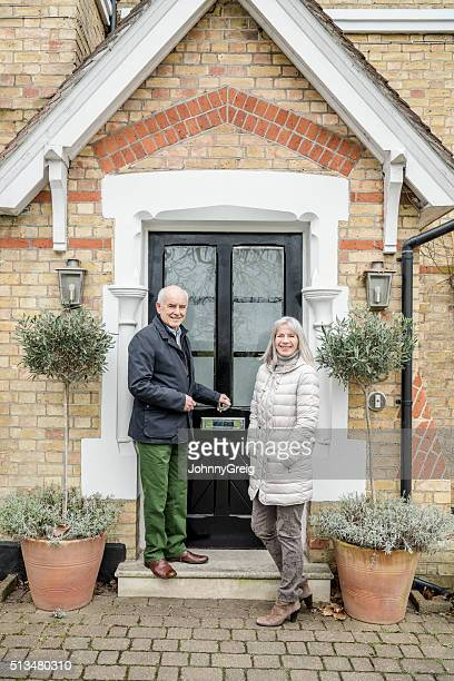 Senior couple standing by porch of house