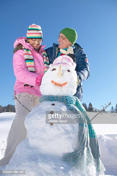 Senior couple standing by snowman, smiling, low angle view