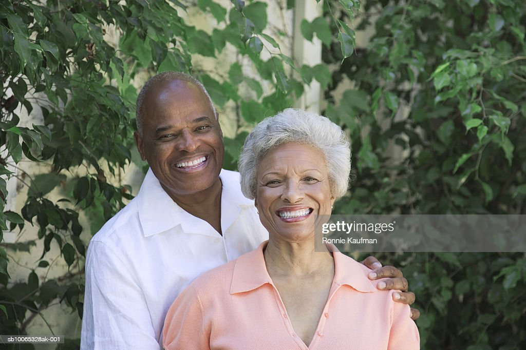 Senior couple standing in domestic garden, smiling : Foto stock
