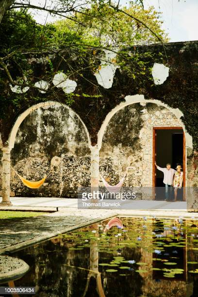 Senior couple standing in doorway of room at luxury tropical resort