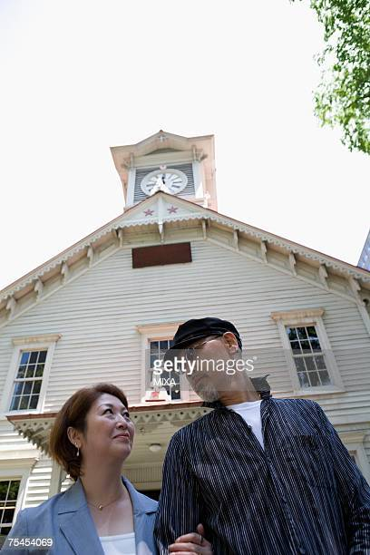 Senior couple standing in front of clock tower