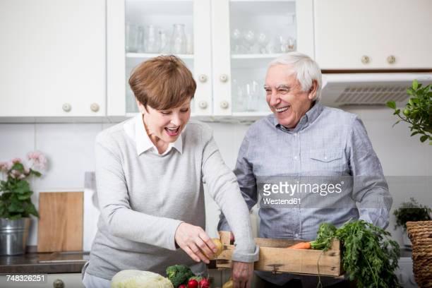 Senior couple standing in kitchen, unpacking fresh vegetables