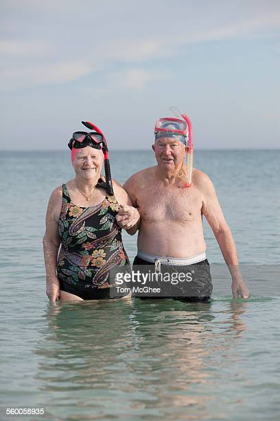 Senior couple standing in water at beach