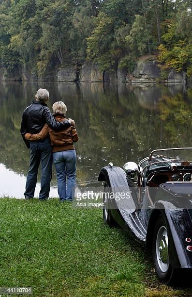 Altes Paar stehen neben dem Teich, in der Nähe von antique car