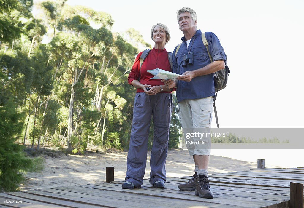 Senior Couple Standing on a Jetty and Holding a Map : Stock Photo